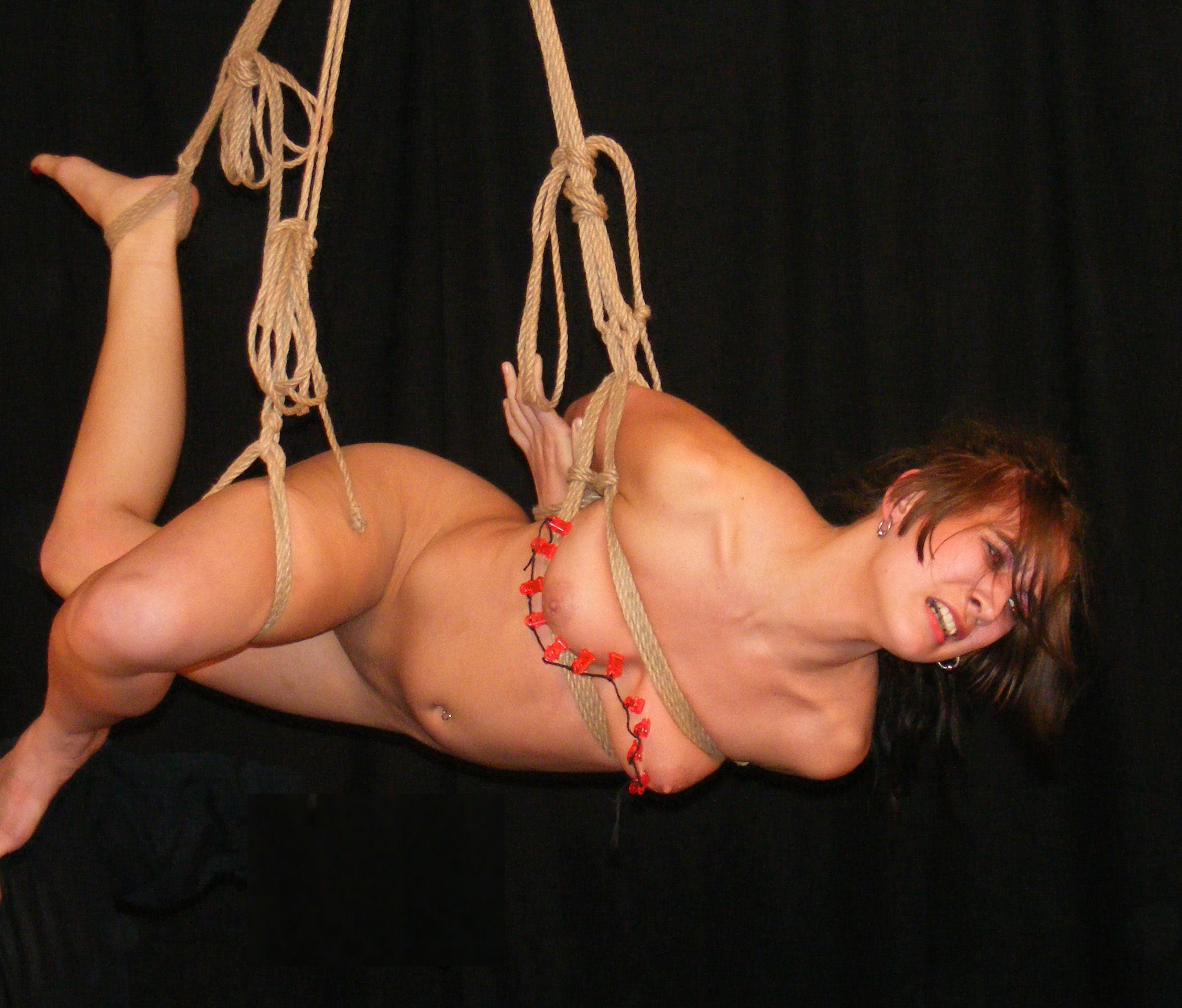 Man and nude girl tied with rope on her knees stock photo